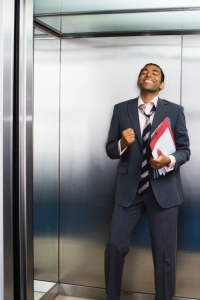 Businessman celebrating in lift